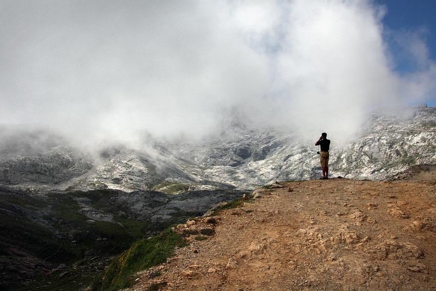 Paisagem de montanha com o nevoeiro a começar a descer. Um home a espreitar com binóculos