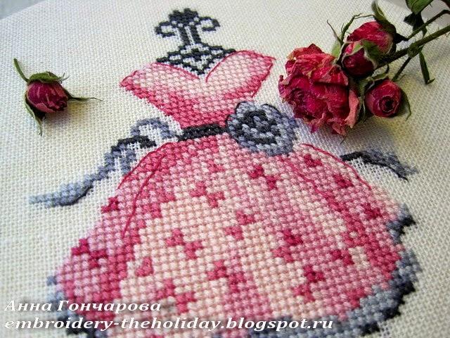 вышивкой платья на вешалке