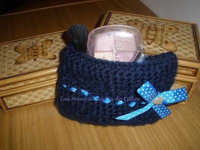 cosmetiquero hecho a crochet con cosas de maquillaje