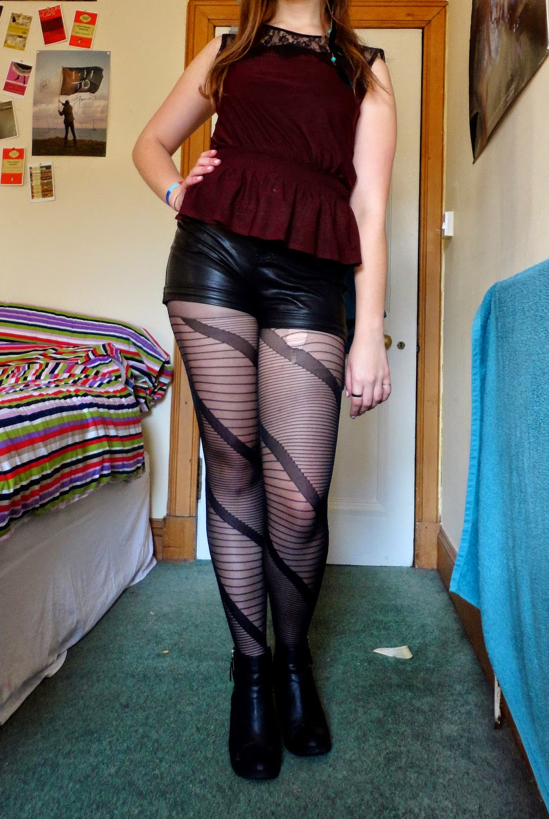 outfit of red peplum top with black lace, black fake leather shorts, striped tights and heeled ankle boots