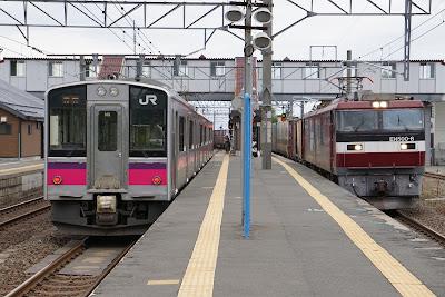 津軽線蟹田駅を通過するEH500形貨物と停車中の701系