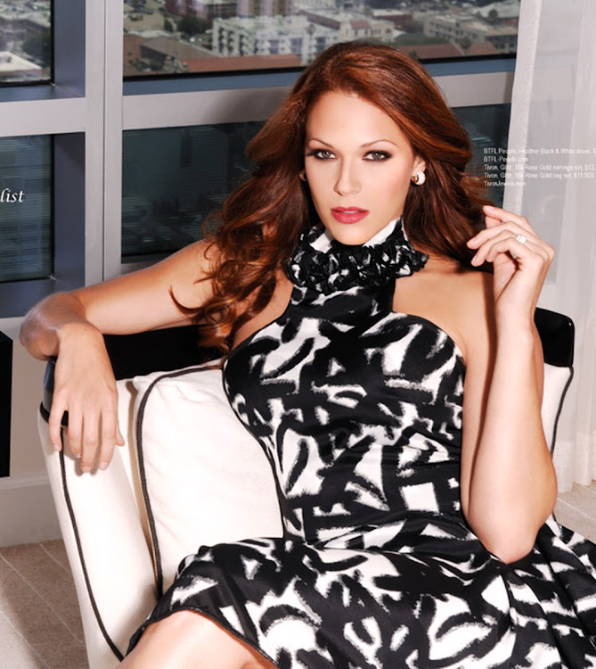 Amanda Righetti wearing abstract print dress and sitting in a chair