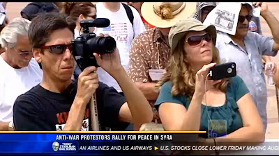 Syd Stevens videotaping and Cristie Paris live-streaming anti-war rally speakers.