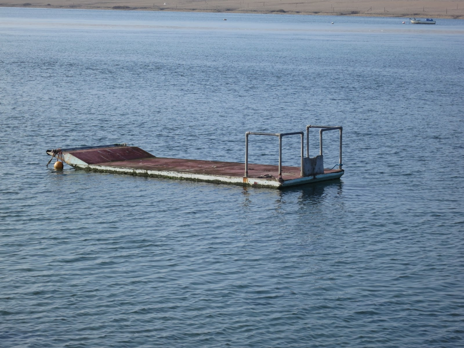 Platform with railing on Fleet Lagoon in Dorset. Blue water with ripples.