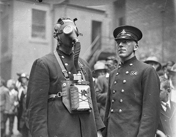 New gas-masks for the NSW Fire Brigade, Castlereagh Street headquarters, Sydney, 1927 / Sam Hood. Firemen display their latest gasmask at the Fire Brigade's Castlereagh Street headquarters, where popular demonstrations for the public were given on Wednesday afternoons.