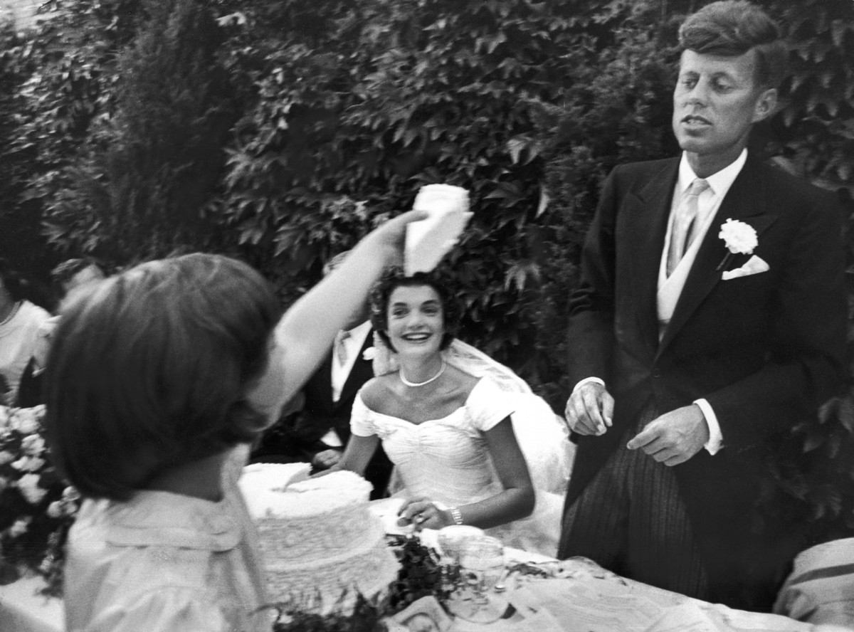 26 candid photographs from the wedding of john f kennedy and flower girl janet auchincloss holding up a wedge of wedding cake for bridegroom sen john kennedy as her half sister bride jacqueline bouvier kennedy looks junglespirit Gallery