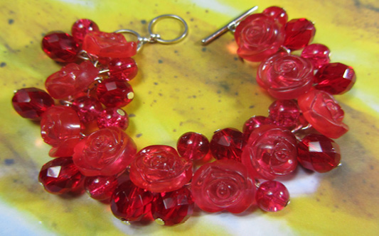 Dramatic bracelet has red flower buttons and clusters of shiny Czech beads