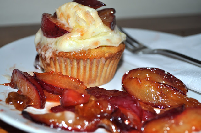 Cupcake mit Vanillebuttercreme und kandierten Pflaumen auf Teller mit weißer Serviette und Gabel angerichtet