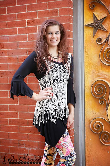 teen girl in black tunic, printed leggings, and crocheted fringed vest
