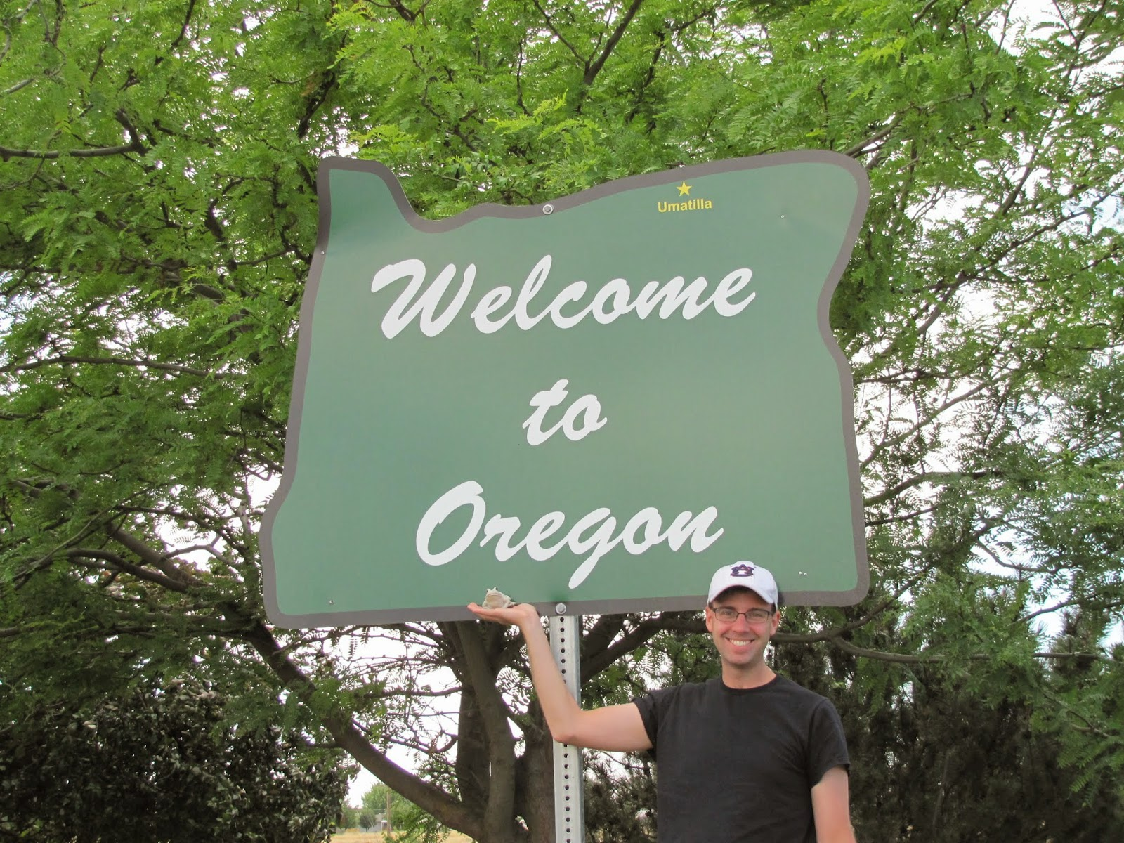 Cory and Frog pose with the Oregon welcome sign