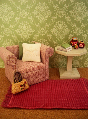 Modern dolls' house miniature pink and white armchair and white side table on a pink woven rug.