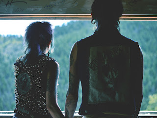punk couple holding hands while looking out a window at a forested hill -- white girl with shaggy blue hair and studded leather jacket, white guy with large ear gauges and a sleeveless shirt