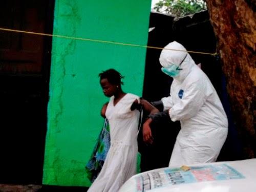 Một nhân viên y tế dìu một người phụ nữ bị nghi nhiễm Ebola lên xe cấp cứu ở Liberia