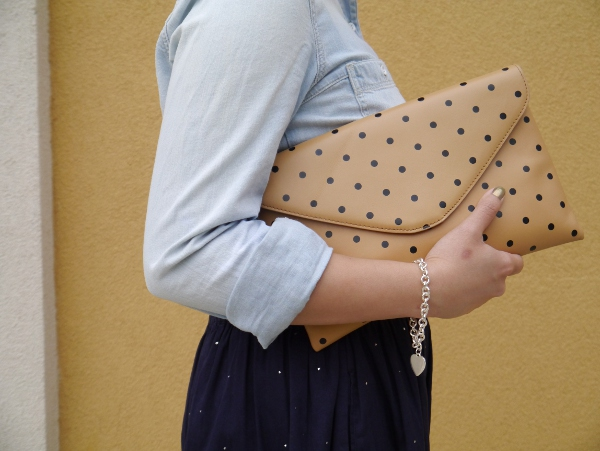 A detailed photo of a Madewell chambray shirt, J. Crew cognac leather belt and polka dot invitation clutch, Chinti and Parker skirt from Vancouver boutique Oliver and Lilly's, and a silver charm bracelet from Birks.