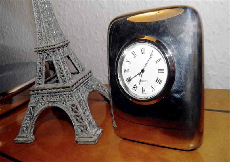 Uhr und Miniatureiffelturm auf dem Schreibtisch
