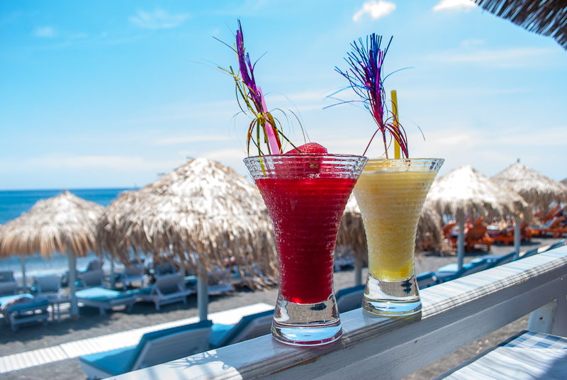 Perissa black beach with drinks in santorini, greece