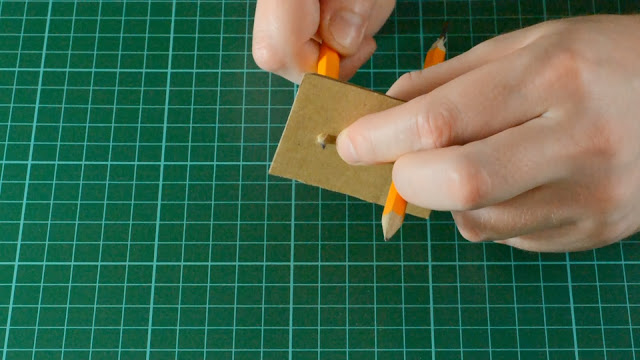 Pierce card to allow pencils through.