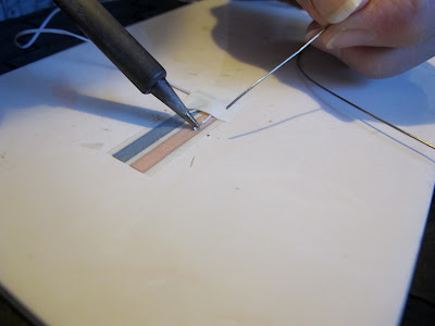Woman soldering a length of wire onto copper tape.