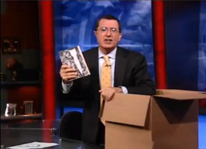 stephen colbert with a box of books