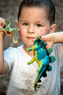 Toddler with toy dinosaurs