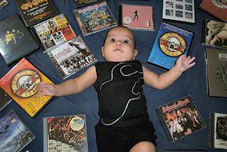 Bebê deitado em meio a discos de bandas de rock famosas