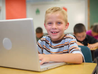 Young boy with laptop in a classroom