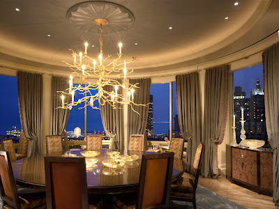 luxurious and stunning round room of dining room which includes round dining table and comfy chairs, stunning gold finished chandeliers, accent soft curtains and view to the city