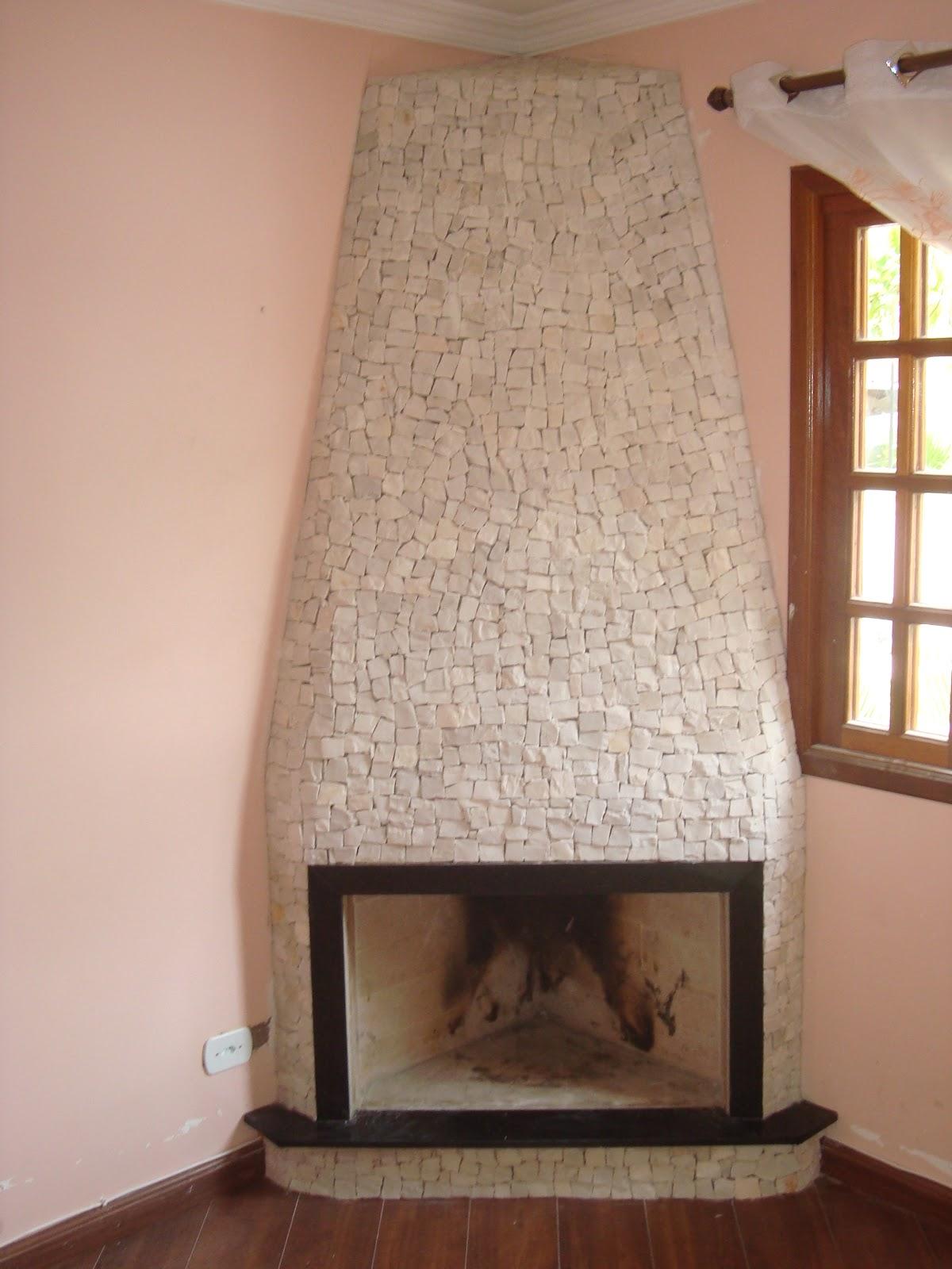 Esta lareira revestida com mosaico branco, pedras selecionadas e