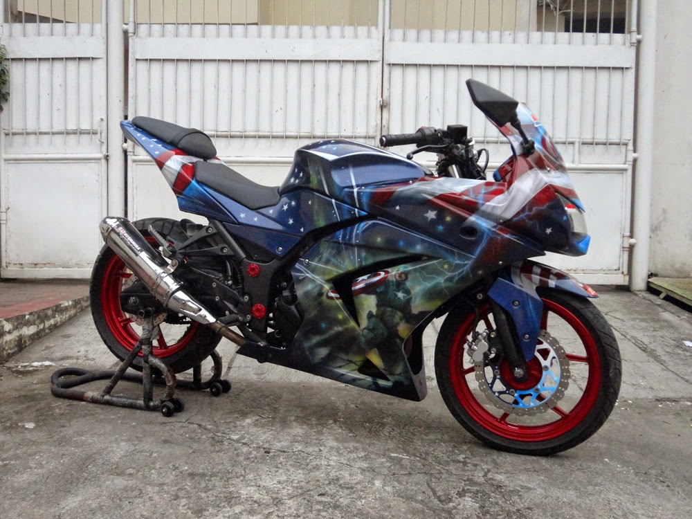 Otosia.net - Tampil beda dan menarik menjadi sebagian besar tujuan modifikasi motor bagi para pecintanya. Seperti penampakan pada modifikasi Kawasaki Ninja 250 yang satu ini, balutan airbrush bermotif bendera Amerika