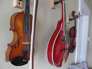 child-sized violins and a mandolin hanging on a wall