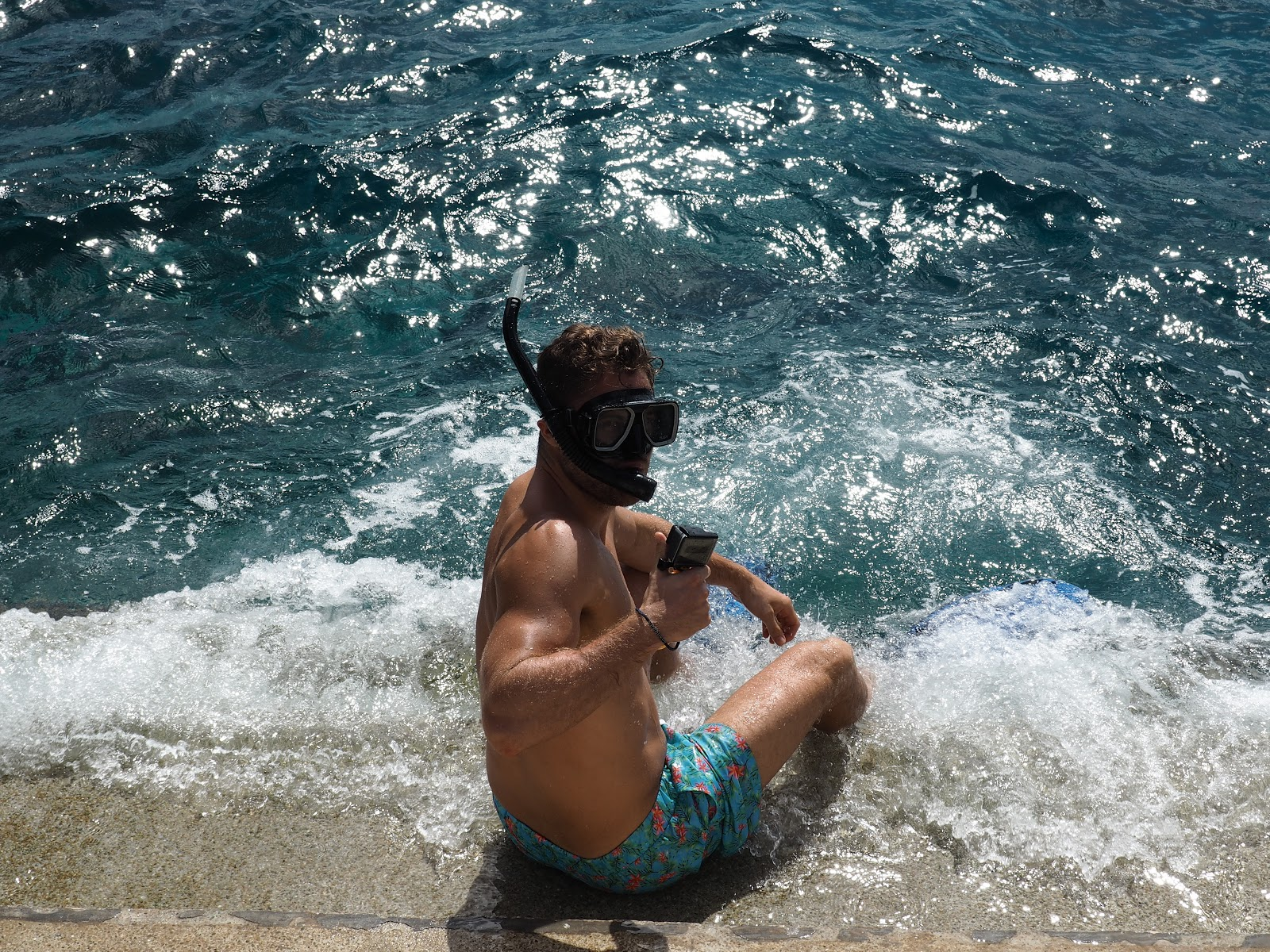 man in sea holding a Go Pro, wearing board shorts and a snorkel