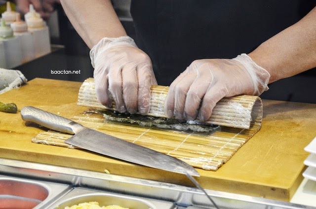 Okonomi prepares the sushi rolls in front of you behind a transparent glass