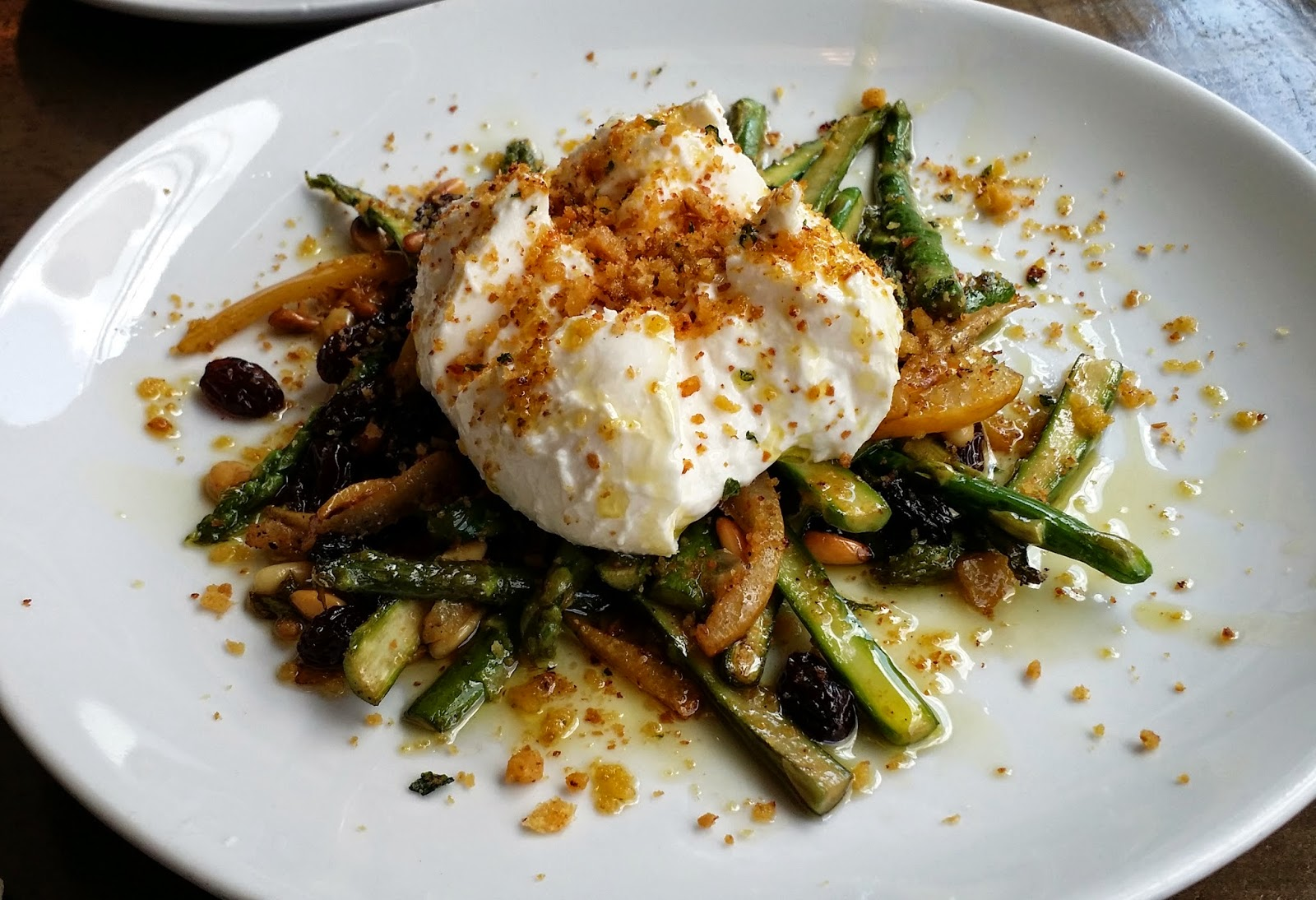 of cold burrata cheese over warm asparagus, pine nuts, golden raisins ...