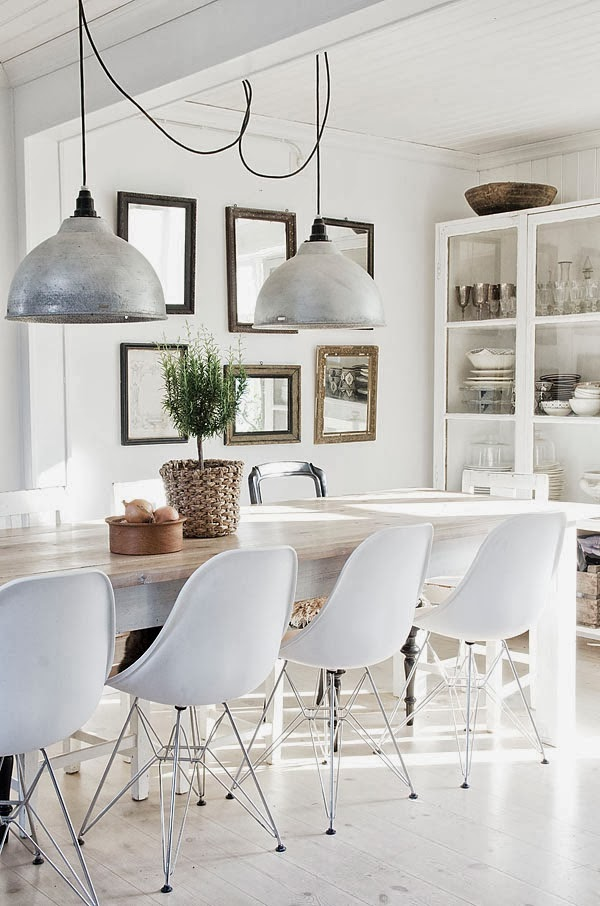 White dining room with Eames chairs and a long table