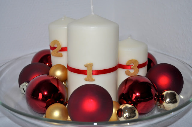a bowl holding the four advent candles and some red and golden balls