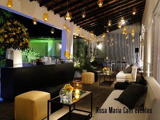 velas teto, sófa branco, almofadas pretas, puff quadrado amarelo, flores amarelas velas flutuantes, parede listrada preta branca, mesa bistrô