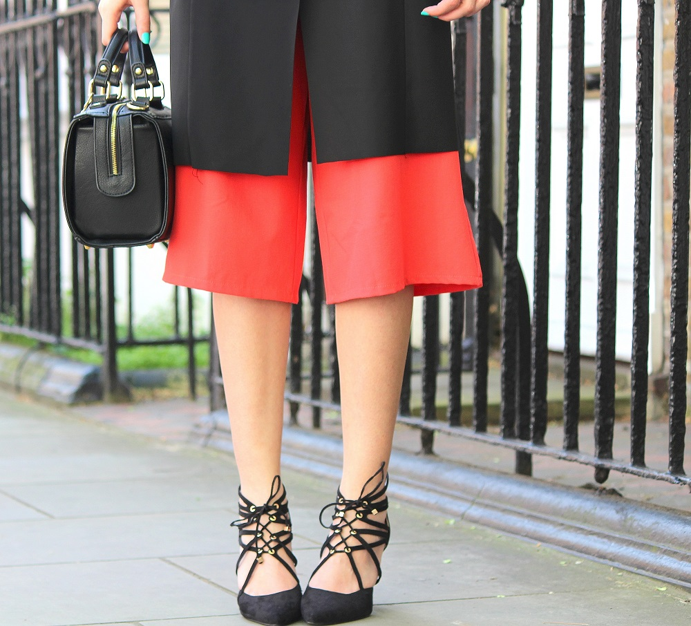 peexo fashion blogger wearing culotte jumpsuit and sleeveless blazer and black box bag and lace up heels in spring