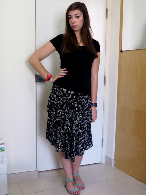 Crazy Daisy | outfit of black top, floaty black daisy pattern skirt & green strappy sandals