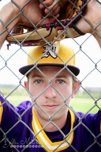 17 year old boy in purple baseball jersey leaning on fence
