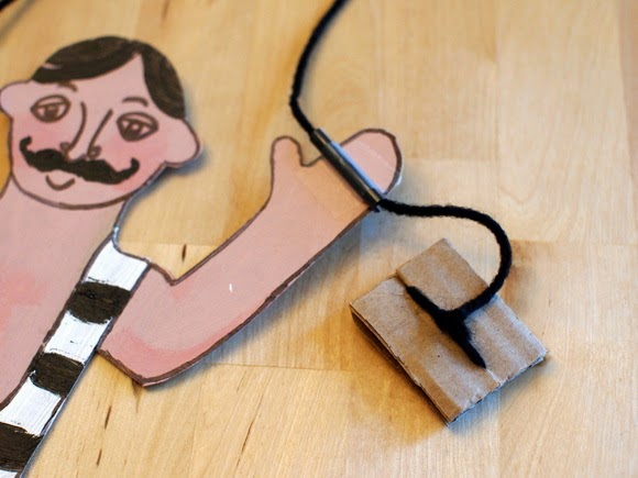 tie a piece of cardboard onto the end of the strings