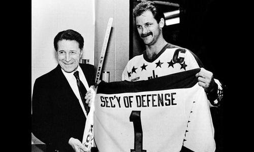 Rod Langway, whose nickname was 'Secretary of Defense', gives a Caps sweater to Secretary of Defense Caspar Weinberger, whose nickname was 'Cap' (Yes, really)