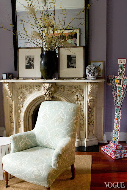 living room with lavender walls, a black mirror, framed portraits of Diego Rivera and Frieda Kahlo, and a marble fireplace mantel with a black and white skull