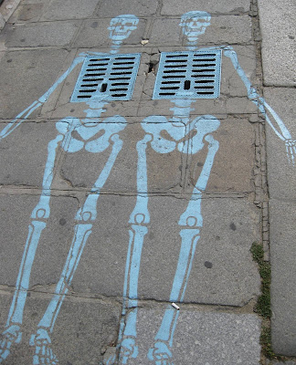 Skeletons drawn on pavement in Paris, near the Hotel des Invalides.