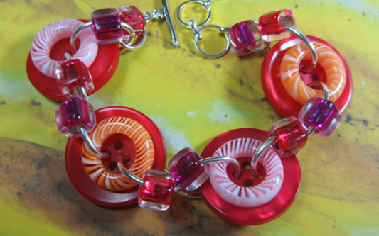 Bold bracelet has big red buttons accented with donut beads and smaller shiny beads