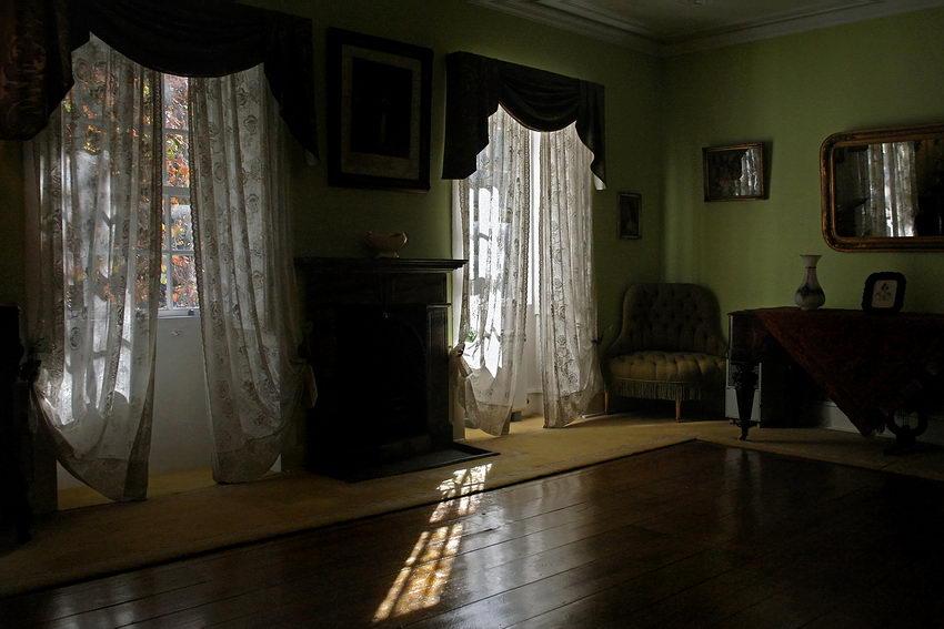 Sala com duas janelas com cortinados, com muita luz tornando o interior muito escuro na foto