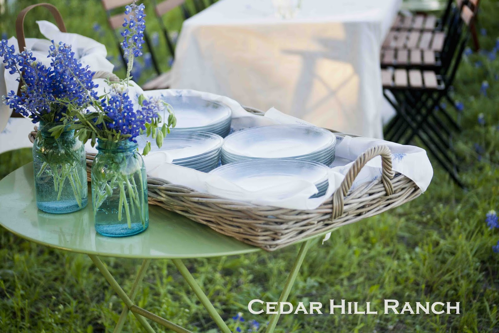 i placed the plates in this very large wicker tray i got at hobby lobby the bluebonnets on this table are in vintage blue mason jars next to that table