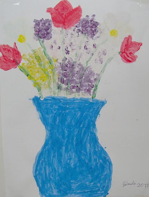 Pintura. Em fundo branco, grande vaso azul com flores coloridas. Vaso centralizado ocupa metade inferior da imagem. De baixo para cima vê-se o vaso, largo na base, estreito no meio e largo na extremidade superior, sete hastes verdes de flores alinhadas lado a lado. Entre as hastes e flores grandes, pequenas flores roxas e amarelas, pontilhismo. Da esquerda para a direita as flores,1 rosa vermelha, 1 flor branca, 1 rosa vermelha, 1 flor branca, e 1 rosa vermelha. Canto inferior direito, escrito Gabriela 2011.