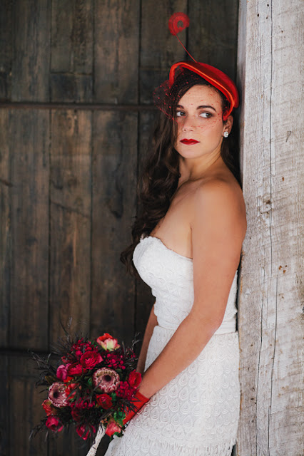 bride with red bouquet, white lace gown