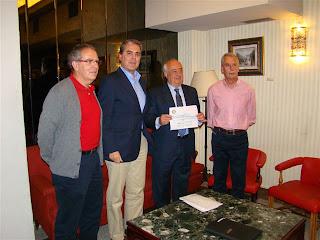 El presidente del Rotary Club entrega al de Cáritas el cheque con la recaudación