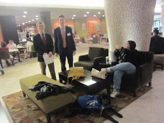 Michele and Coach are sitting in the lobby area as two of our students stand and look on (Max and Jake).